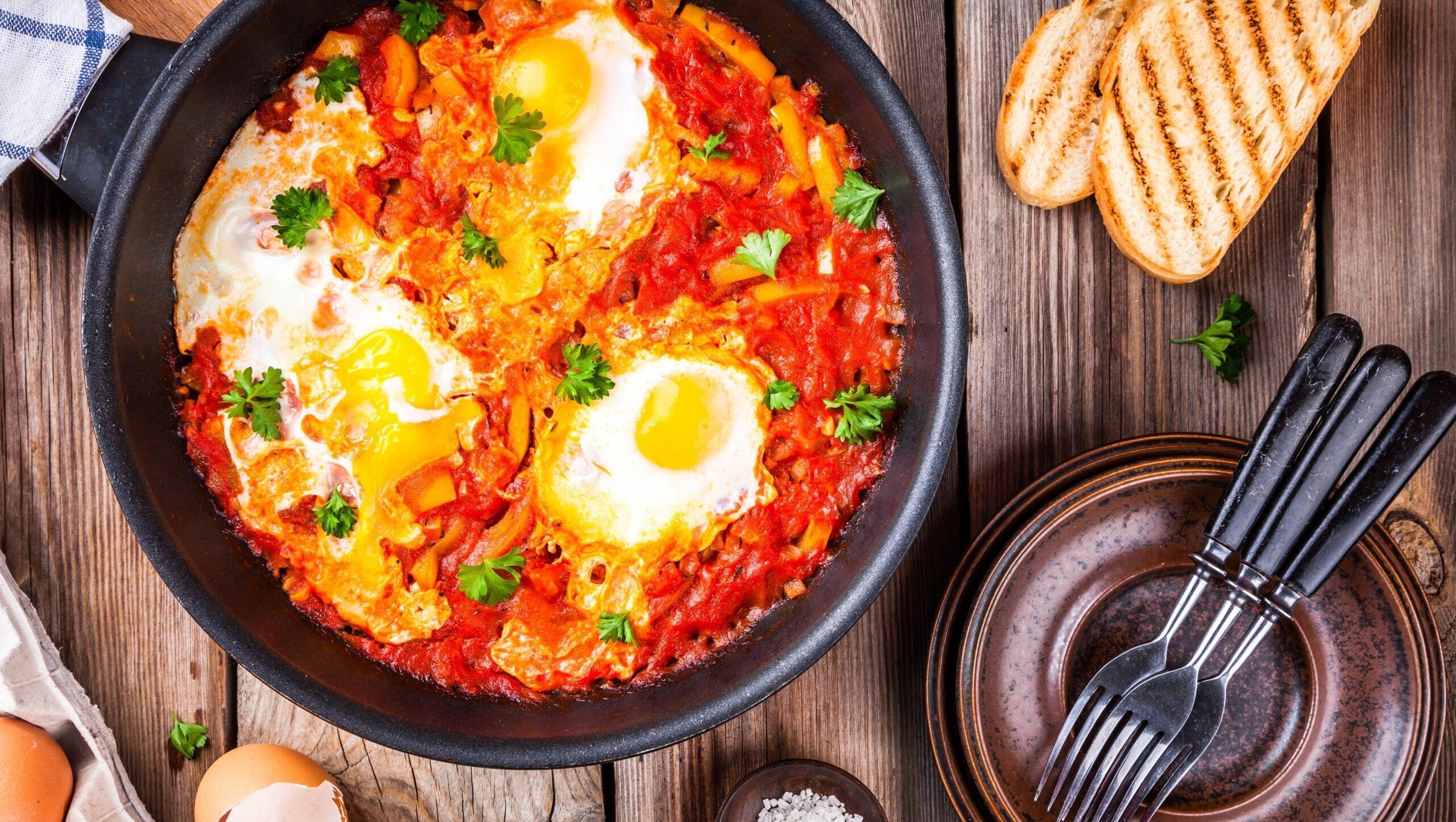 Shakshuka. Fried eggs with tomato,